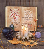 Satanic rites 1. Old book with mystic symbols and black skull Royalty Free Stock Image