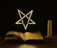 Pentacle on the wall dark. Old book with mystic symbols and candle royalty free stock images