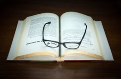 Old book open and eyeglasses Royalty Free Stock Images