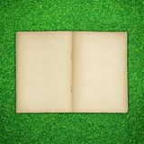 Old book open on green grass Royalty Free Stock Photo