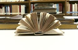 OLD BOOK OPEN. PICTURE OF OLD BOOK OPEN WITH OLD BOOKS BEHIND royalty free stock images