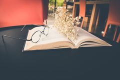 Old book open on table with reading glasses and classic flower. Old book open on table with reading glasses and classic flower stock image