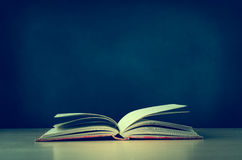 Old Book Opened on Desk with Chalkboard in Background - Retro Ve Royalty Free Stock Photos