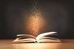 Free Old Book Opened On Desk With Sparkling Stars Rising Upwards Royalty Free Stock Image - 172886496