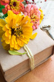 Old book with orange zinnia, key and autumn berries Royalty Free Stock Image