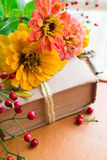Old book with orange zinnia, key and autumn berries Stock Image