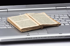 Old book over computer. Open old book over computer keyboard Royalty Free Stock Photos