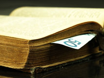 Old book and paper money. Royalty Free Stock Image