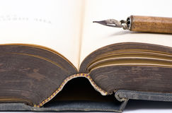 Old book and pen. An old book that is open with a calligraphy pen on top royalty free stock photos