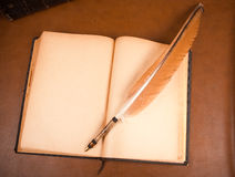 Old book and quill pen. Old book and gavel on leather desktop Stock Photos