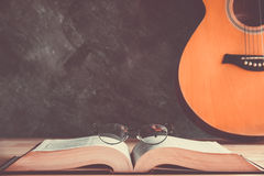 Old book. With reading glasses and guitar background Stock Images