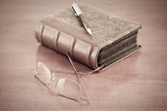 Old book with reading glasses and pen Royalty Free Stock Images