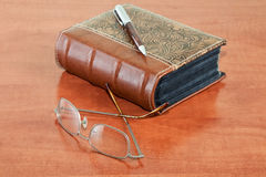 Old book with reading glasses and pen Stock Image