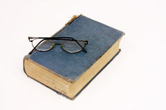 Old book with reading glasses resting on white. A very old history book with reading glasses, on a white background royalty free stock photography