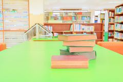 Old book red - green. heap are interior library school on wooden table and blurry bookshelves background. Royalty Free Stock Image