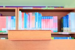 old book red in school library on wooden table. blurry bookshelves background Royalty Free Stock Image