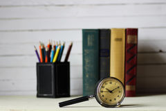 Old book retro watch. Old book and retro watch on white wooden table Stock Photo