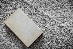 Old book on rustic carpet texture Royalty Free Stock Photo