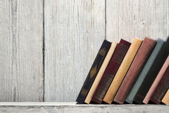 Old book shelf blank spines, empty binding stand on wood texture Royalty Free Stock Photography