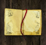 Old book with ship silhouettes Royalty Free Stock Image