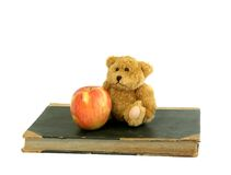 Old book, small bear and apple isolated on white Stock Image
