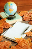 Old book with small globe on it and notebook with ink pen near maple leaves on the able Royalty Free Stock Photos