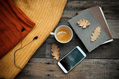 Old book,smart phone , autumn leaves  on wooden background. Conc Royalty Free Stock Photos