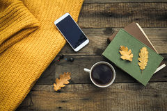 Old book,smart phone , autumn leaves  on wooden background. Conc Royalty Free Stock Photo