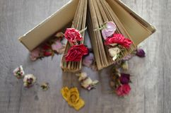 Old book standing on wooden table and dried roses. Royalty Free Stock Image