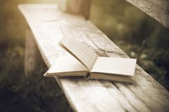 Old book of stories lying on a wooden bench stock image