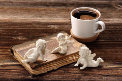 Old book, the three angels and cup of coffee Royalty Free Stock Photos