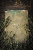 Old book with thyme on the wooden table vertical Royalty Free Stock Images