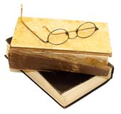 On an old book with a torn binding and a broken spine are glasses. Isolated on white stock photography