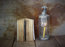 Old book and vintage lamplight on wooden table Stock Images