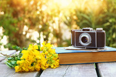 old book, vintage photo camera next to field flowers Royalty Free Stock Image