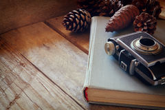 Old book, vintage photo camera next to pine cones Stock Photos
