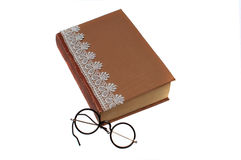 Old book and vintage round reading glasses. On a white background Stock Images