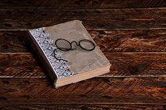 Old book and vintage round reading glasses. On a wooden background Royalty Free Stock Photography