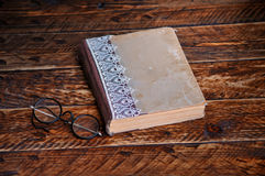 Old book and vintage round reading glasses. On a wooden background Stock Images