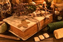 Old Book With Four-leaf Clover, Candles, Herbs And Runes On Witch Table Royalty Free Stock Images