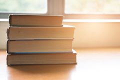 Book on wood table. textbook beside window. education, study con. Old book on wood table. textbook beside window. education, study concept Royalty Free Stock Photos