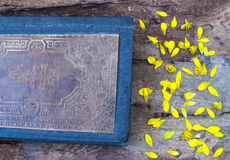 Old book on a wooden background texture. Religion and Christianity,yellow flower petals,rough , fond Royalty Free Stock Image