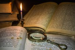 Old book on a wooden table by candlelight stock images