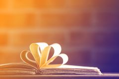 Old book on wooden table at fairy lights background. Library Stock Photo