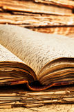 Old Books. Close-up of script writing on pages inside an old open book resting on more pages and with books in the background Stock Images