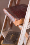 Old books on aged white ladder royalty free stock photography