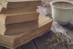 Old books along with a cup of coffe royalty free stock images