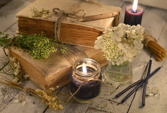 Old books with black candles and healing herbs and flowers