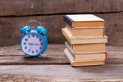 Old books and blue alarm clock. Stock Photography
