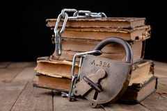 Old books bound by a new shiny chain with an old padlock. Forbidden old works artists on a wooden table
